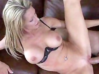 mature bleached sits down on soft sofa and